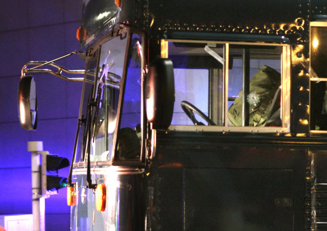 Image: A bullet hole is seen in the driver's window as the bus is towed away after a gunman fired shots at U.S. soldiers