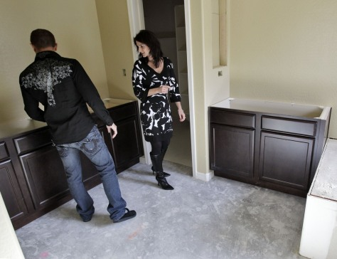 Image: Katie and Mike Zwanziger look at the master bathroom in their new home in Gilbert, Ariz