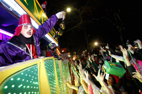 Revelers scream for beads as members of the Krewe of Endymion parade down New Orleans' St. Charles Avenue on Sunday, as part of the city's Mardi Gras celebrations.