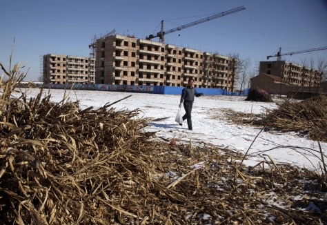 Image: A Chinese farmer walks past the half completed apartment blocks built to relocate the farmers from Damazizhuang village in northern China's Hebei province