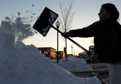 Image: A woman shovels the sidewalk in front of her house in Glens Falls, N.Y