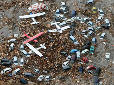 Image: Cars and airplanes swept by a tsunami are pictured among debris at Sendai Airport, northeastern Japan