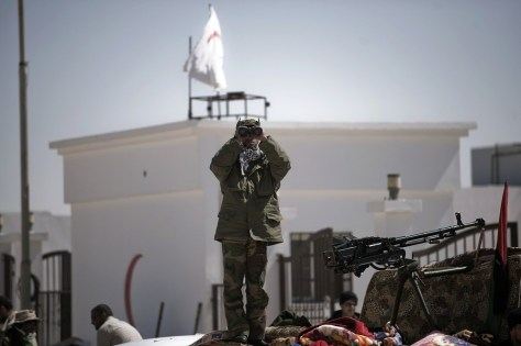 Image: A Libyan rebel fighter atop a truck scans the skies for fighter jets.