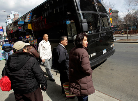 Image: Passengers in Manhattan's Chinatown neighborhood in New York wait to board a bus