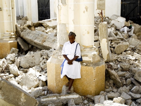 Image: A woman stands inside the destroyed cathedral in Port-au-Prince after attending a mass