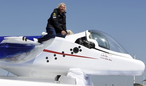 Image: Sir Richard Branson sits on top of a solo piloted submarine during a photo opportunity at a news conference in Newport Beach