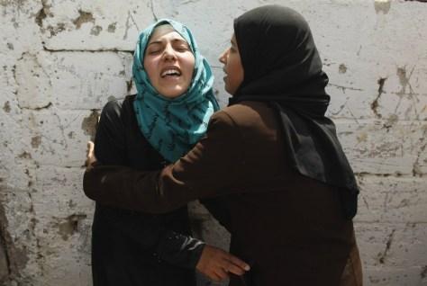 Image: Palestinian relatives of Hamas militant Abdalah Al-Kara mourn during his funeral in Khan Younis