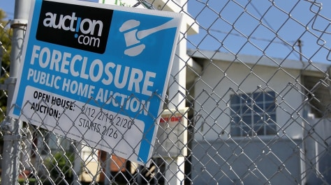 Image: A foreclosure sign hangs on a fence in front of a foreclosed home in Richmond, Calif.