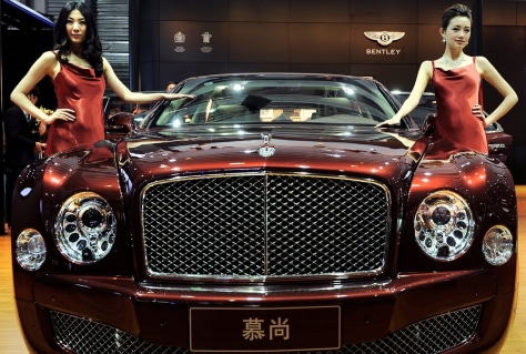 Image: Models pose next to a Bentley