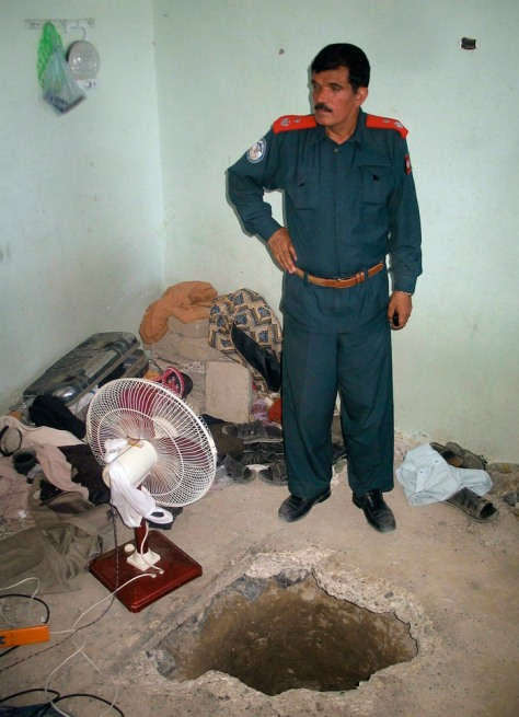 Image: Afghan jailer Ghulam Dastager Mayaar stands next to the hole which the inmates used to escape from inside the Kandahar's main jail
