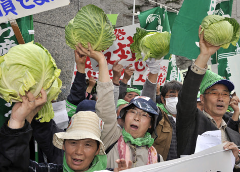 Image: Farmers hold cabbages to protest against the Japanese nuclear accident at the headquarters of the Tokyo Electric Power Co (TEPCO) in Tokyo on April 26.
