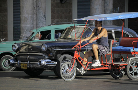 Image: A man looks for customers on his tricycle taxi in Havana