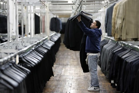 Image: A worker hangs suits