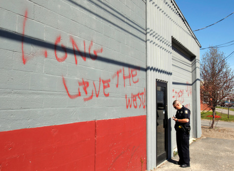 Image: Police officer stands next to the graffiti-covered Maine Muslim Community Center in Portland