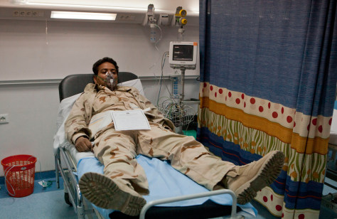 Image: A Libyan soldier wearing an oxygen mask lies at Khadra Hospital in Tripoli