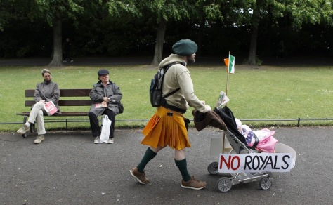 Image: A baby stroller adorned with signs of protest against the upcoming visit of Britain's Queen Elizabeth is pushed through St. Stephen's Green in Dublin
