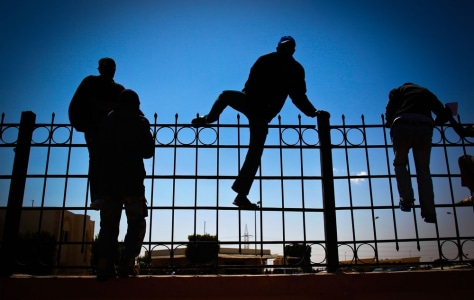 Image: People span the guardrail of customs at the Libyan-Egyptian border crossing of Sallum.