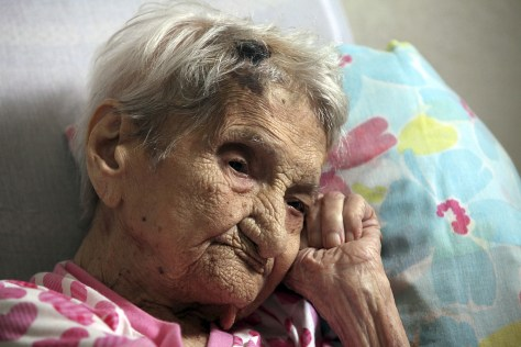 Image: Maria Gomes Valentim, 114, lies on her bed in Carangola