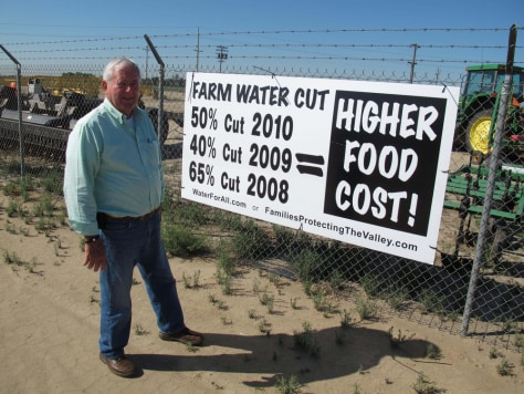 Image: Joe Marchini of Marchini Farms stands in front a water cutbacks sign on the flanks of his field