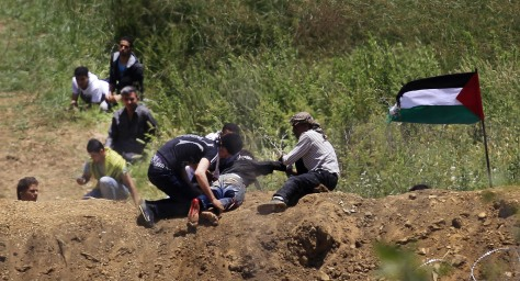 Image: A wounded protester is dragged away from the Syrian-Israeli border near Majdal Shams in the Golan Heights