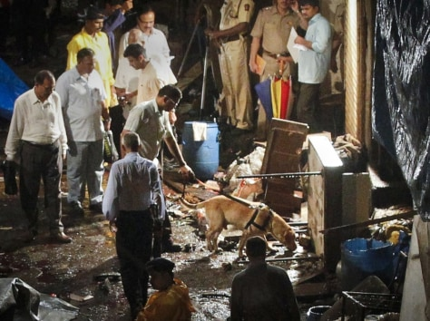 Image: Police use a sniffer dog after an explosion in the Zaveri Bazaar in south Mumbai