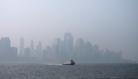 Image: A thick haze hangs over the skyline of Lower Manhattan as a ferry crosses the Hudson River in New York