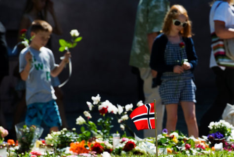 Image: Children leave roses at a makeshift memorial outside the Cathedral in Oslo