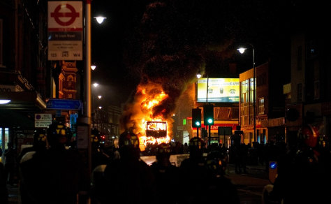 Image: A double decker bus burns Saturday as riot police try to contain a large group of people on a main road in Tottenham, north London
