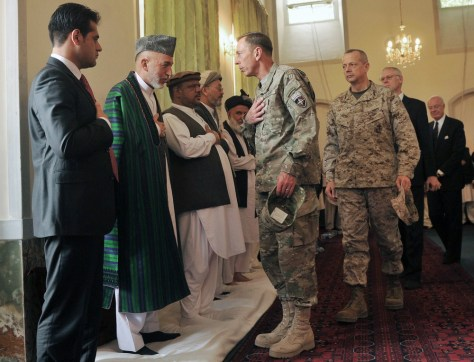 Image: Afghanistan's President Hamid Karzai greets General Petraeus during the funeral ceremony for his younger brother Karzai at the presidential palace in Kabul
