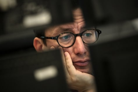 Image: A stockbroker works at the stock exchange in Frankfurt, Germany
