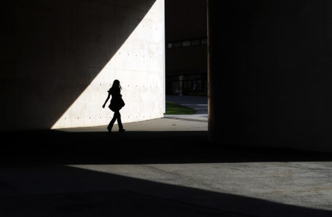 Image: A student walks between buildings at the School of Engineering and Applied Sciences at Harvard University in Cambridge