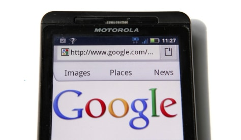 Image: A Google homepage is displayed on a Motorola Droid phone in Washington