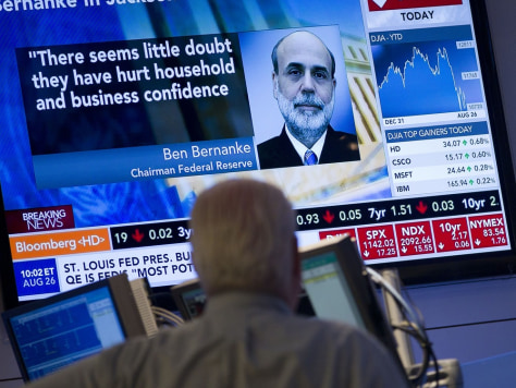 Image: A trader looks up at monitor after Federal Reserve Chairman Ben Bernanke's speech
