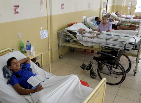 Image: People intoxicated from tainted alcohol, lie in bed at the general hospital in Ricaurte, Ecuador