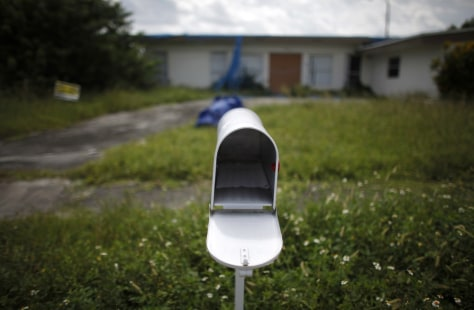 Image: An empty mail box is seen at the front door of a foreclosed house in Miami Gardens