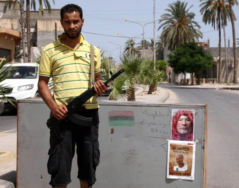 Image: A Libyan rebel stands next to a road block with pictures of Libya's fallen leader Moammar Gadhafi
