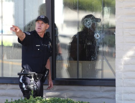 Image: With bullet holes seen in a window, officers look for evidence at the scene of a shooting at an IHOP restaurant in Carson City, Nev.