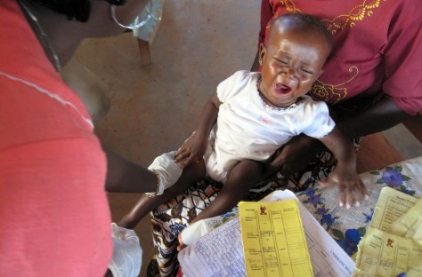 A woman has her child vaccinated at Sembehon outreach station clinic near Bo, in Sierra Leone.