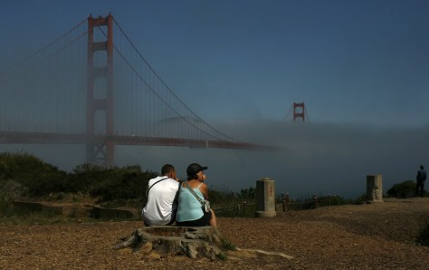 Image: A couple looks out at the fog-shrouded Golden Gate Bridge in San Francisco, Calif.