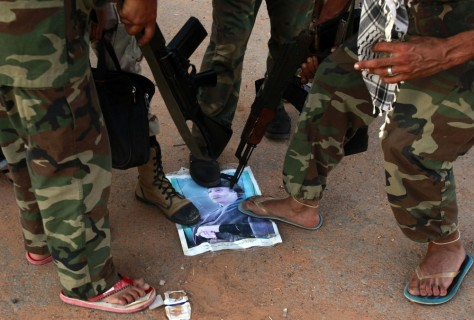 Image: Anti-Gadhafi fighters step on a picture of Moammar Gadhafi that they found with a family fleeing the fighting in Sirte