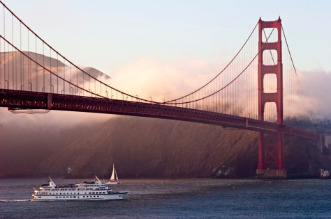 Image: Ferry and sailboat pass under the Golden Gate Bridge at sunset, San Francisco