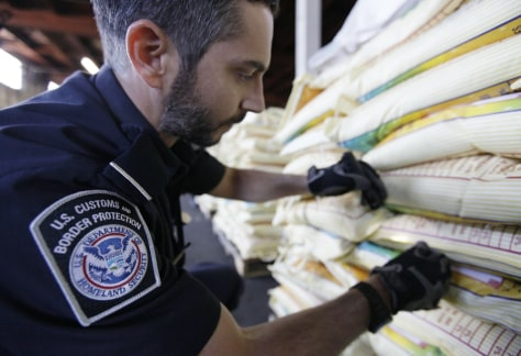 Image: Agriculture specialist Mark Murphy, with U.S. Customs and Border Protection, examines bags of rice during an inspection in Oakland, Calif.