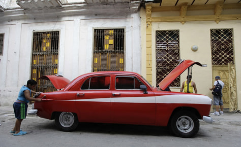 Image: A boy cleans his father's car on a street in Havana