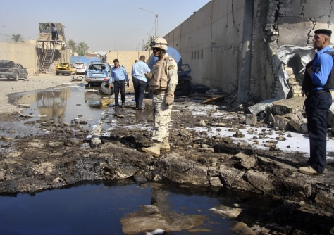Image: A soldier and policemen inspect the site of a bomb attack at a police station in Baghdad's Hurriya district
