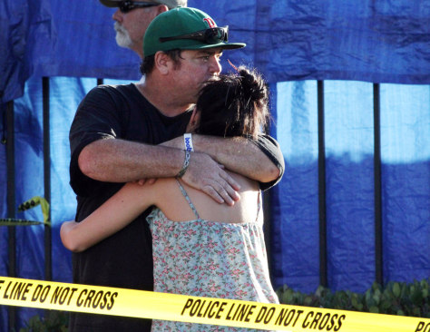 Image: People embrace near the scene of the deadly shooting.