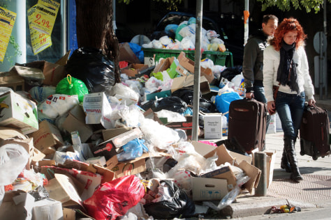 Image: People pass by piles of garbage