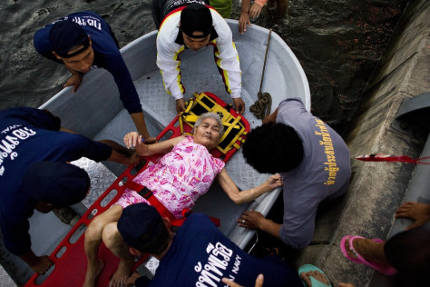 Image: Rescuers in Thailand help and elderlly woman