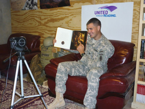 Image: Capt. Peter Hofman records a video of himself reading a story to send home to his kids.