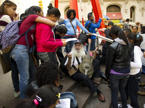 Image: Dennis Gronim talks and plays the guitar for Bronx students visiting Occupy Wall Street on Thursday in Zuccotti Park, New York.