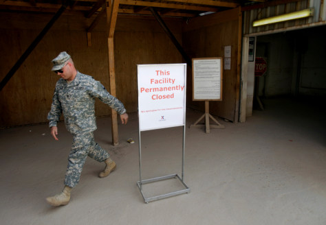 A U.S. Army soldier walks past a sign outside a base exchange after its closure at Camp Victory in Baghdad, Iraq.